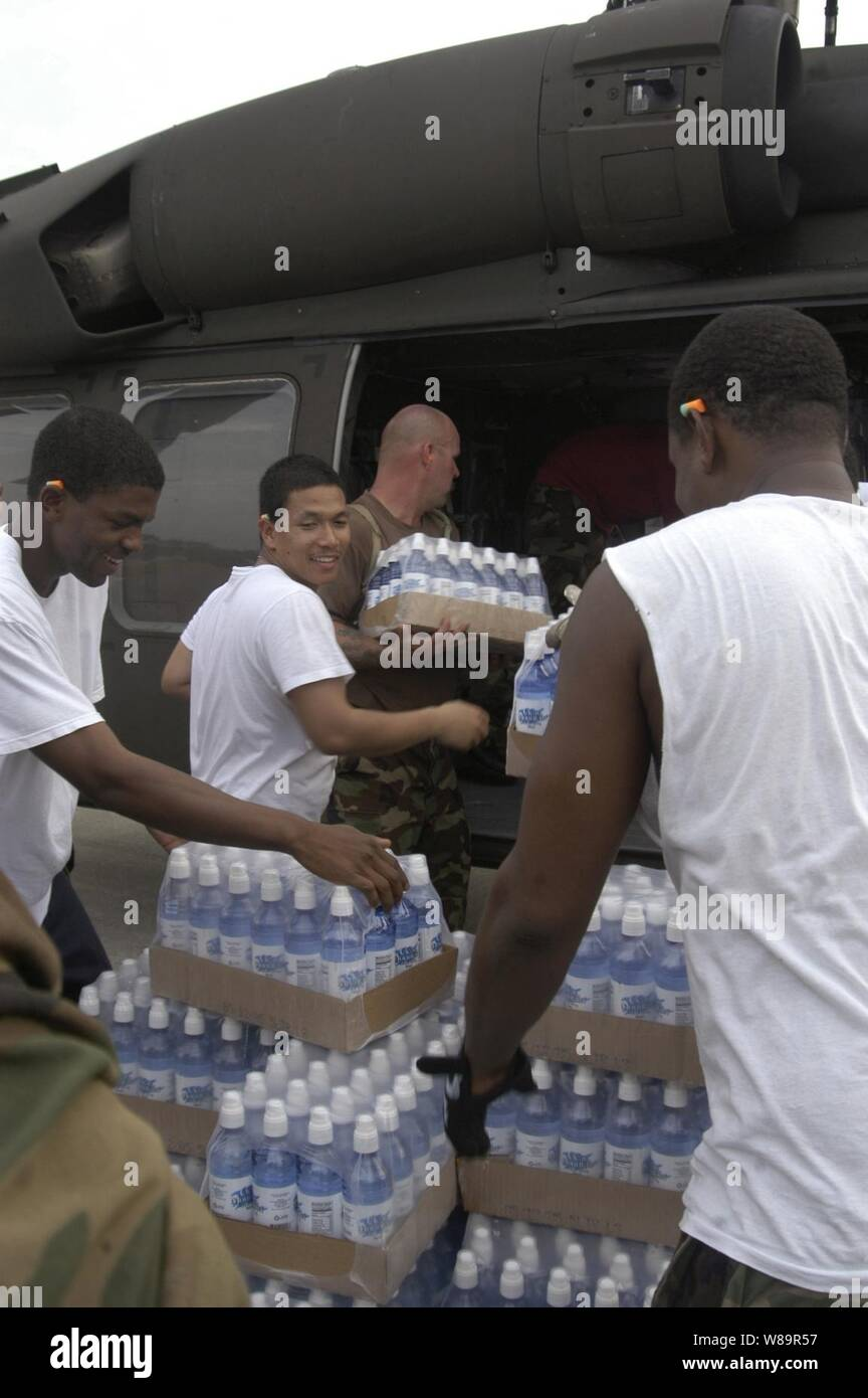U.S. Navy sailors and U.S. Army National Guard members load water and ice into a UH-60 Black Hawk helicopter at Gulf Port International Airport in Biloxi, Miss., on Sept. 1, 2005.  Department of Defense units are mobilized as part of Joint Task Force Katrina to support the Federal Emergency Management Agency's disaster-relief efforts in the Gulf Coast areas devastated by Hurricane Katrina.  The airport is now one of the main staging areas for hurricane-relief efforts in Mississippi.  The sailors are from the USS Bataan (LHD 5) that is operating in the Gulf of Mexico approximately 100 miles sou Stock Photo