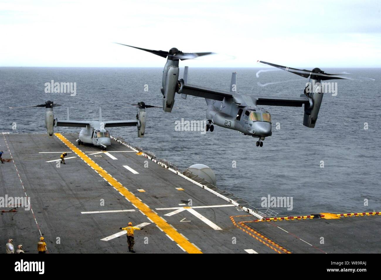 A U.S. Marine Corps MV-22B Osprey executes a vertical take off from the flight deck of the amphibious assault ship USS Wasp (LHD 1) as another waits to launch during flight operations in the Atlantic Ocean on Nov. 15, 2005.  The Osprey is an advanced technology, vertical/short takeoff and landing multipurpose tactical aircraft and is scheduled to replace the aging CH-46E Sea Knight and CH-53D Sea Stallion helicopters currently in service.  These Ospreys are assigned to Marine Tiltrotor Operational Test and Evaluation Squadron 22 of Marine Corps Air Station New River, N.C. Stock Photo