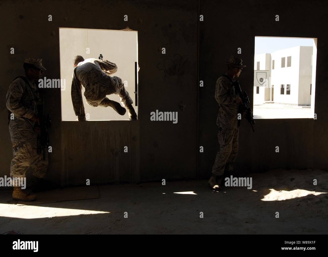 U.S. Marine Corps Lance Cpls. Travis Beckford (left) and Kyle Nance and Cpl. Ryan Burke (right), all from the 4th Platoon, Fleet Anti-terrorism Security Team, advance through buildings during a bilateral urban assault training in Sheik Isa, Bahrain, on Nov. 20, 2008.  The Marines are deployed to the U.S. Navy 5th fleet area of operations in support of maritime security operations. Stock Photo