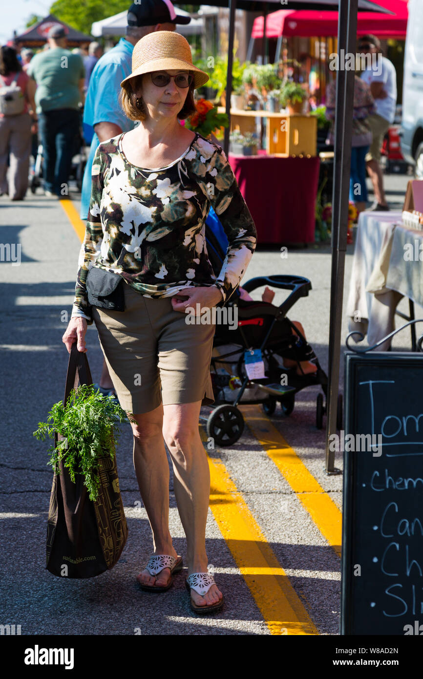 A classy lady carries her purchase in her bag while shopping at Fort Wayne's Farmers' Market in downtown Fort Wayne, Indiana, USA. Stock Photo