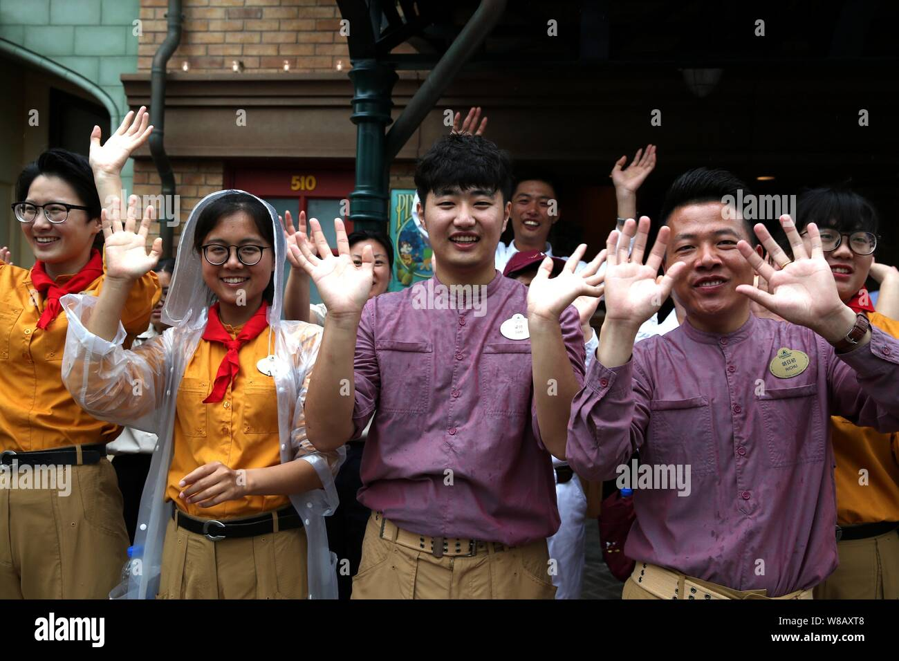Employees wave to tourists during the opening ceremony of the Shanghai Disneyland at the Shanghai Disney Resort in Pudong, Shanghai, China, 16 June 20 Stock Photo