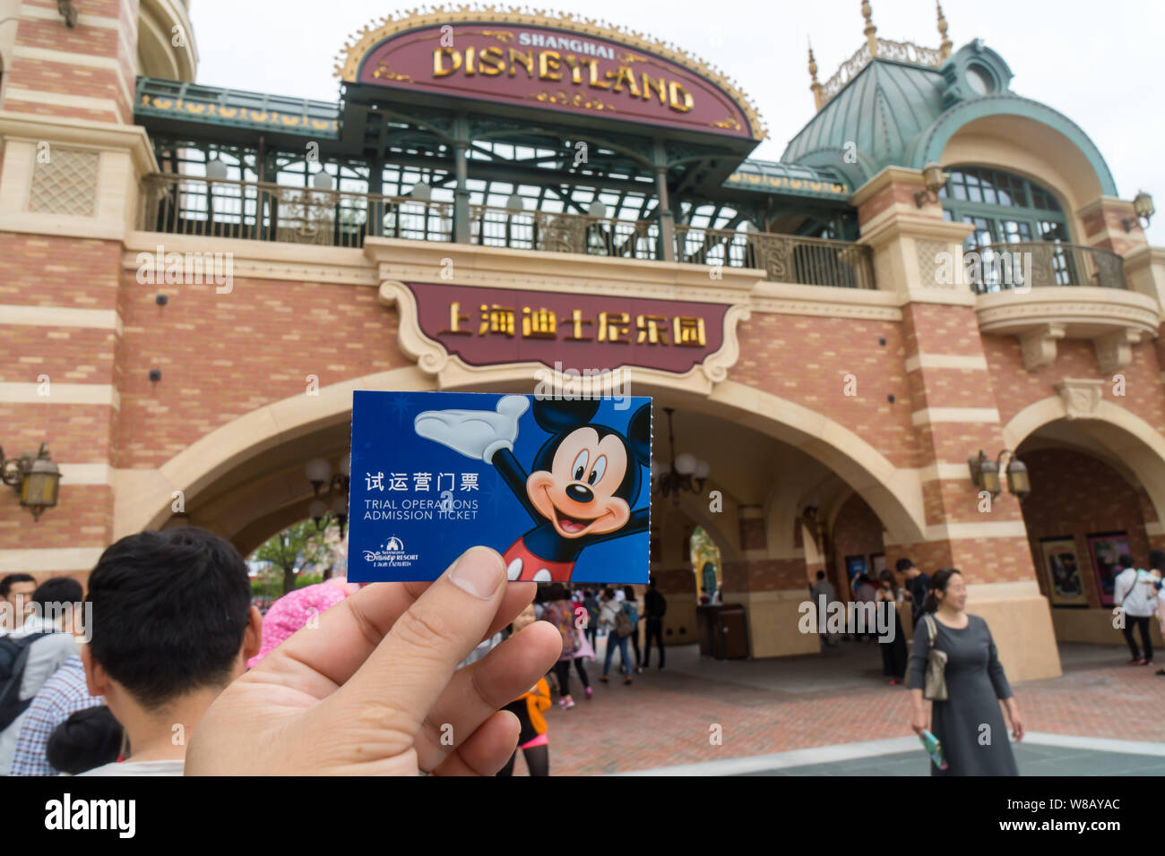 A tourist shows his trial operations admission ticket as he visits the Shanghai Disneyland during the trial operation at the Shanghai Disney Resort in Stock Photo