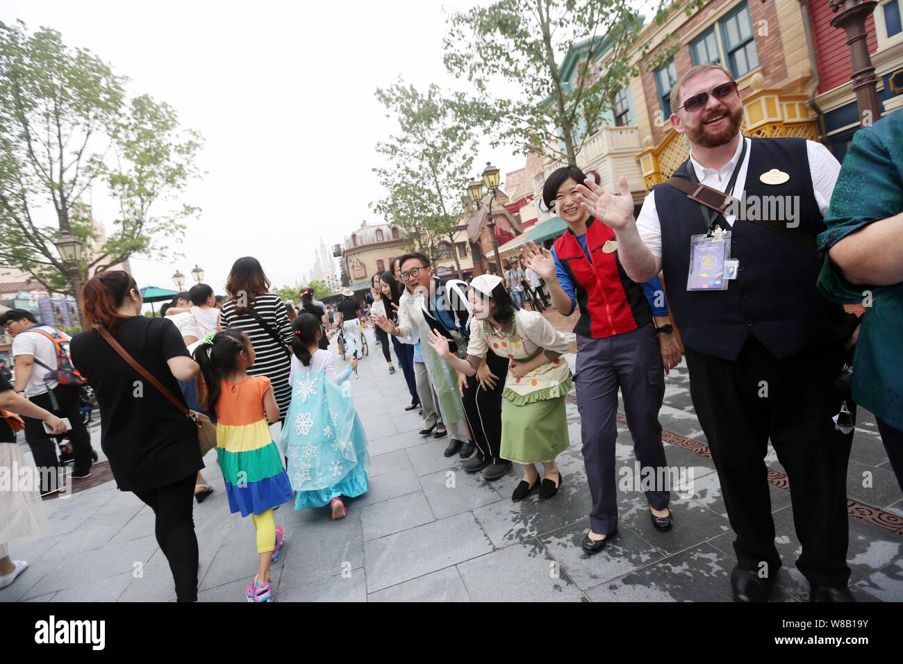 Employees wave to tourists in the Shanghai Disneyland at the Shanghai Disney Resort in Pudong, Shanghai, China, 16 June 2016.   In a rain-dampened cer Stock Photo