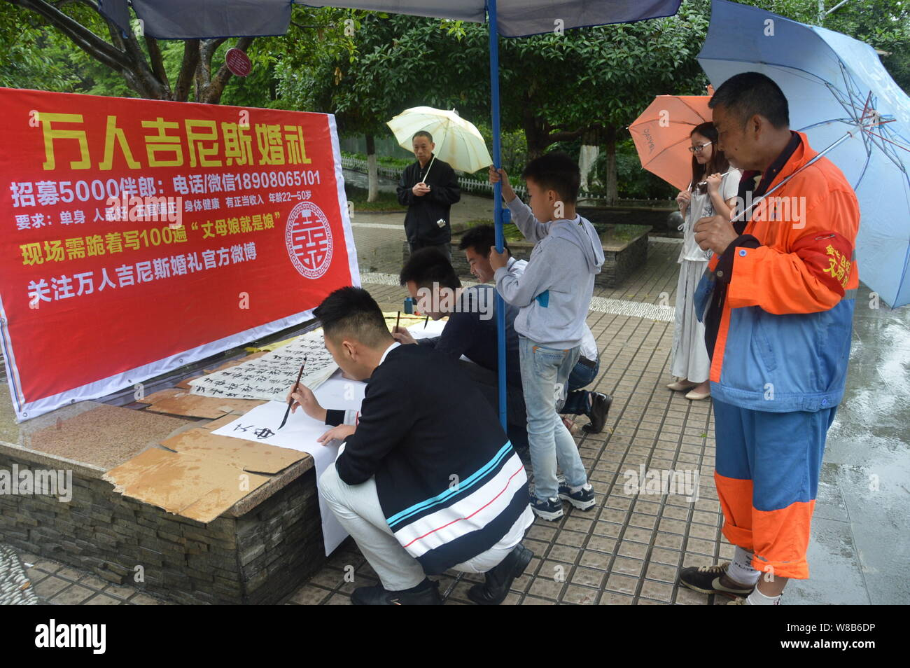 """Chinese applicants write a slogan """"Mother-in-law is mother"""" during a recruitment event for 5,000 best men for a grand wedding featuring 10,000 best me Stock Photo"""