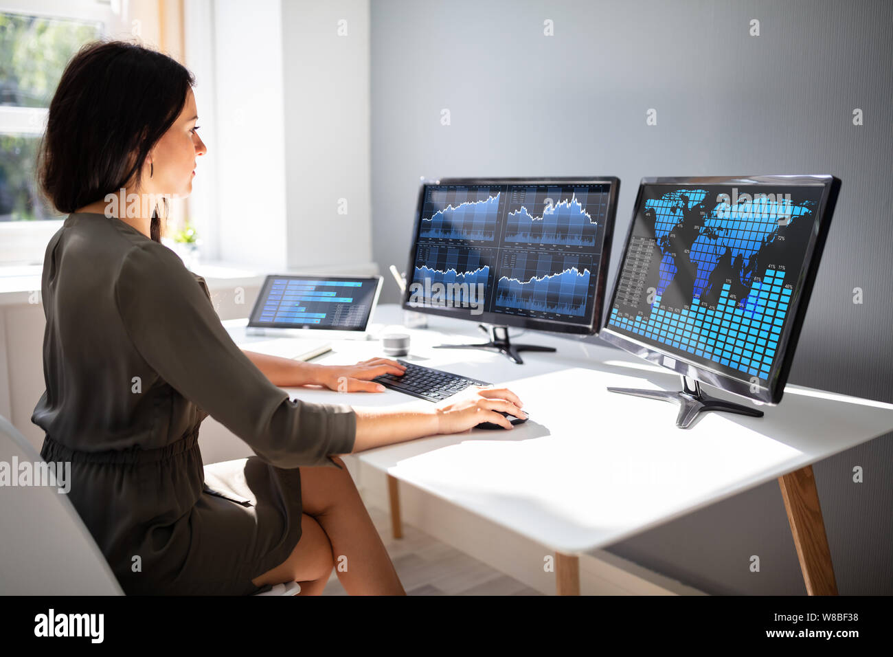 Young female stock market broker analyzing graph on computer at workplace Stock Photo