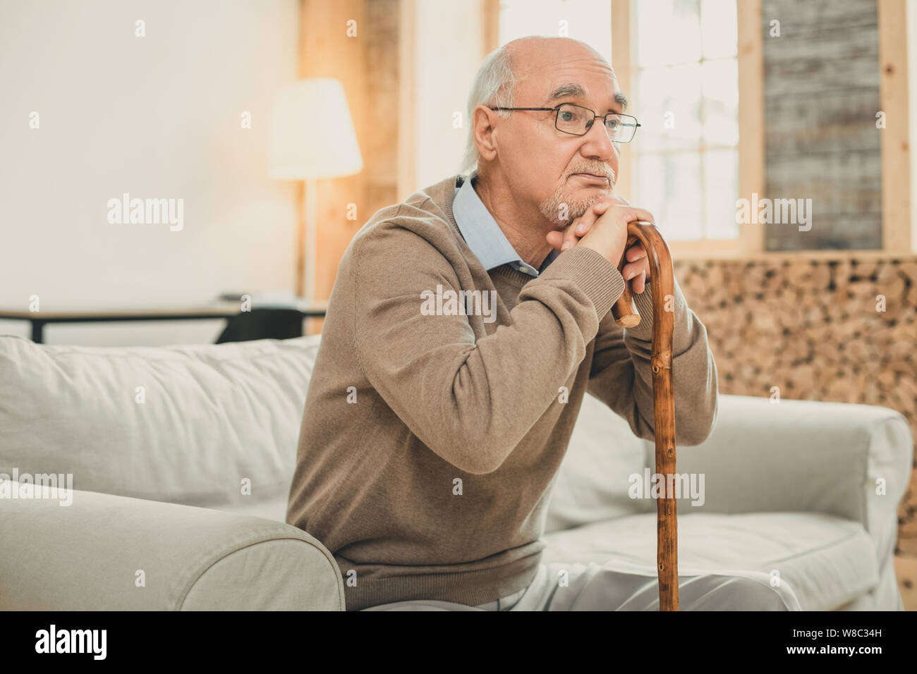 Tired old man with grey hair leaning on the wooden cane Stock Photo
