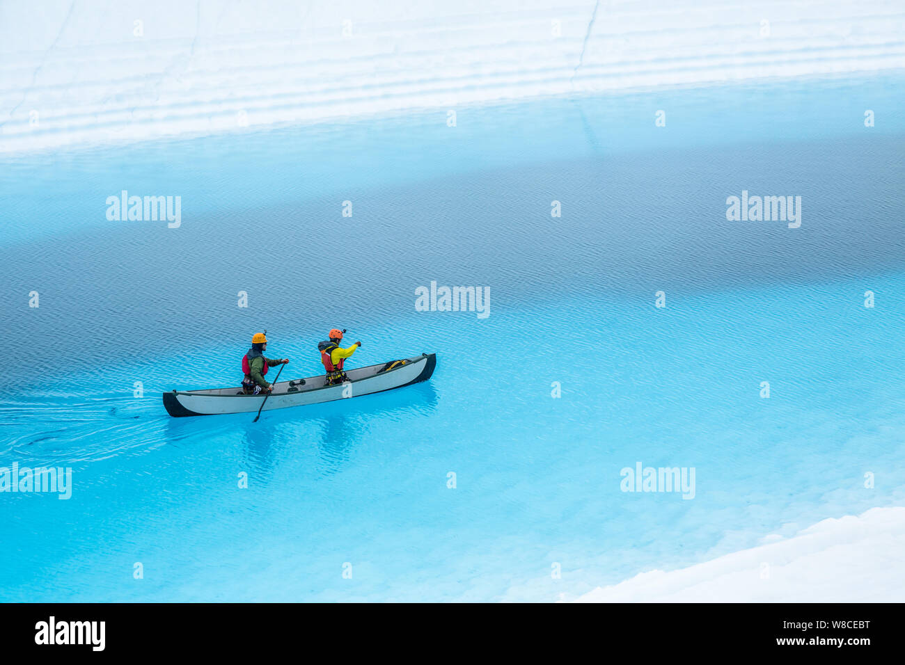Two men paddle an inflatable canoe on top of a blue pool on the Matanuska Glacier in the wilderness of a Alaska. The blue lake is a supraglacial lake, Stock Photo