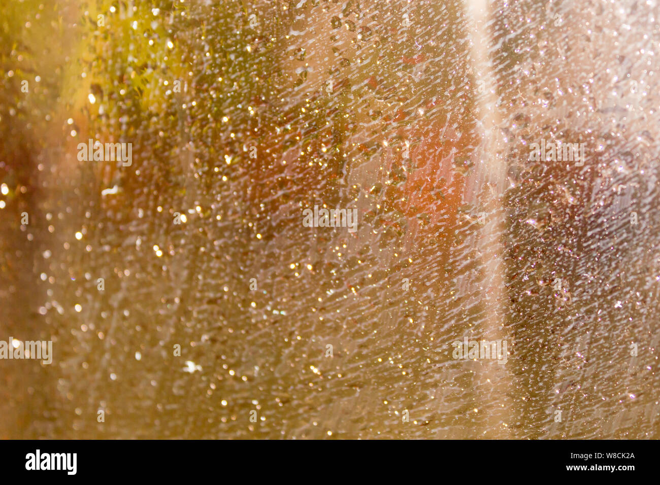 Rain Drops On Surface of wet Window Glass pane In Rainy Season. Abstract background. Natural Pattern of raindrops isolated from outdoor cloudy environ Stock Photo