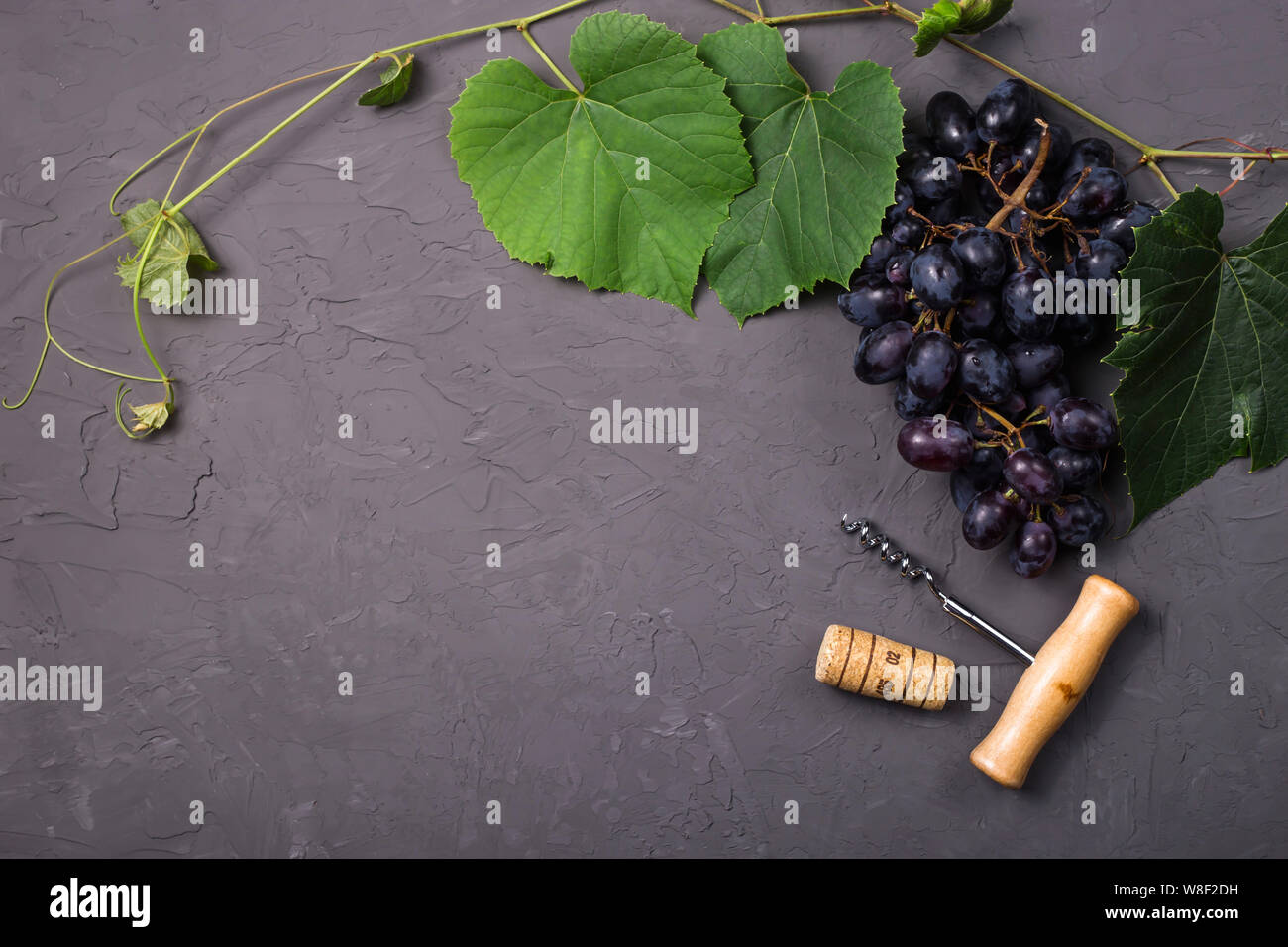 A bottle of red wine next to ripe grapes with leaves on a gray background. Top view, flat lay, copy space Stock Photo