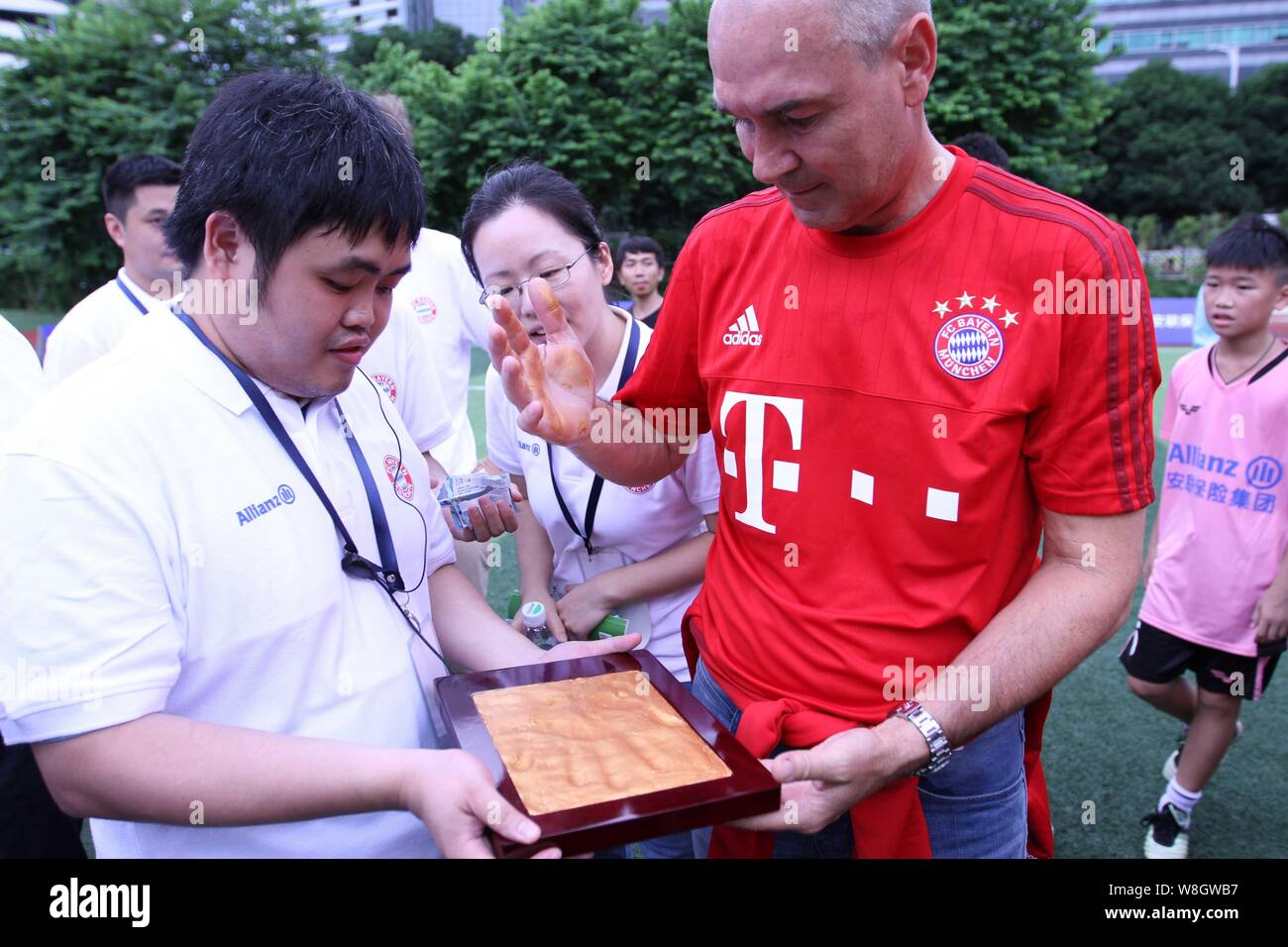 Former German soccer star Raimond Aumann, right, leaves his handprint during a fan meeting event in Guangzhou city, south China's Guangdong province, Stock Photo