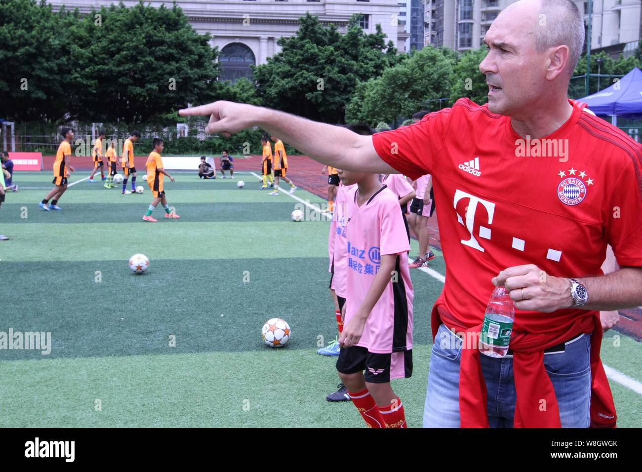 Former German soccer star Raimond Aumann, right, instructs students to play football during a fan meeting event in Guangzhou city, south China's Guang Stock Photo