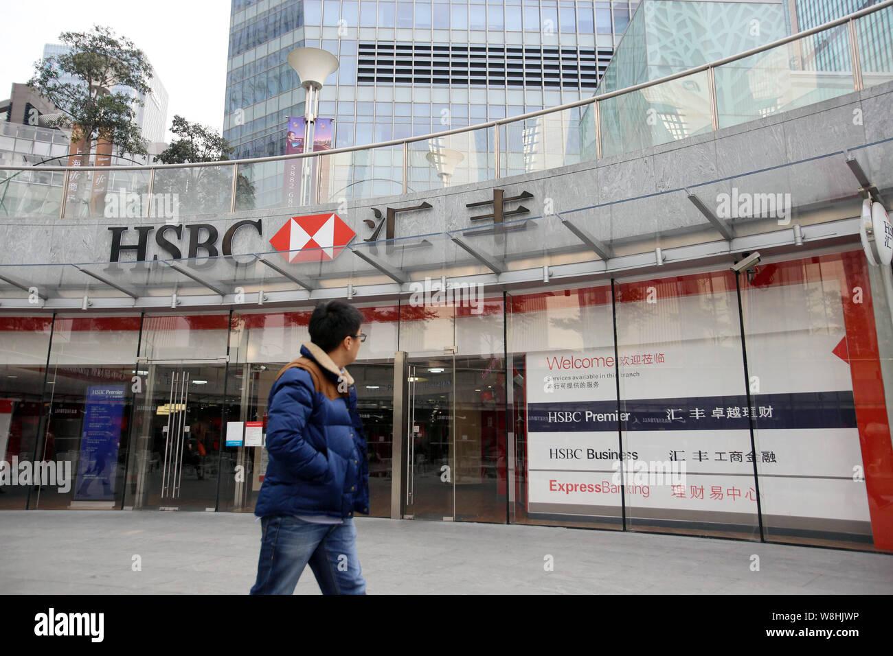 A pedestrian walks past a branch of HSBC (the Hongkong and