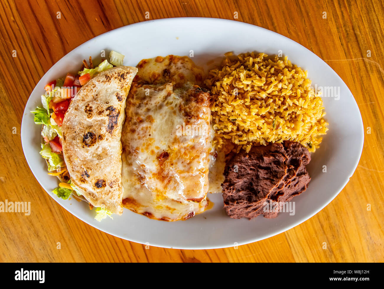 Chicken Enchilada plate with rice, beans and chicken taco Stock Photo