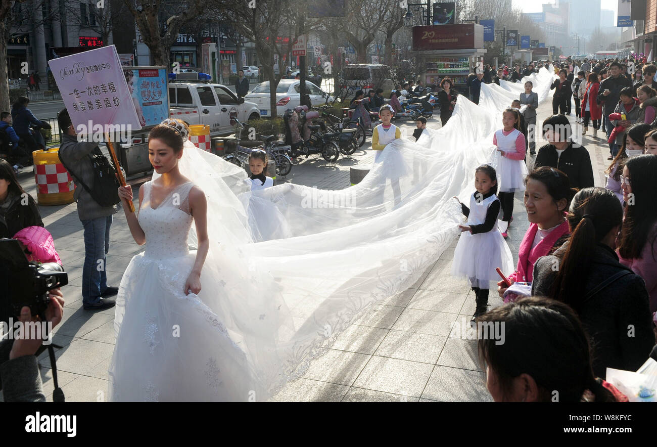 A Model Wearing A Bridal Gown With A 101 Meter Long Tail Carried
