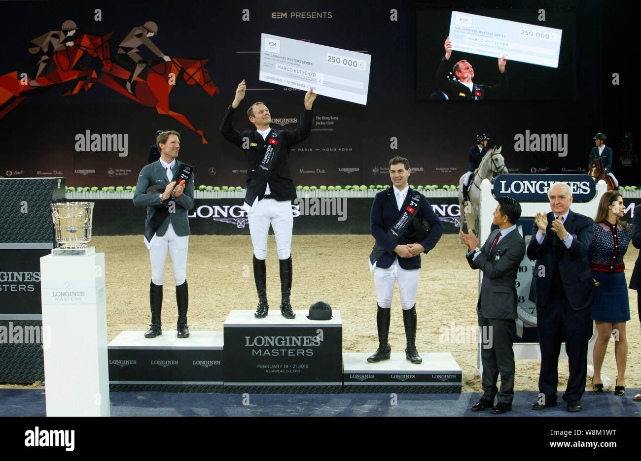 Macro Kutscher of Germany, second left, holds up his bonus cheque after winning the show jumping Longines Masters Grand Prix during the award ceremony Stock Photo