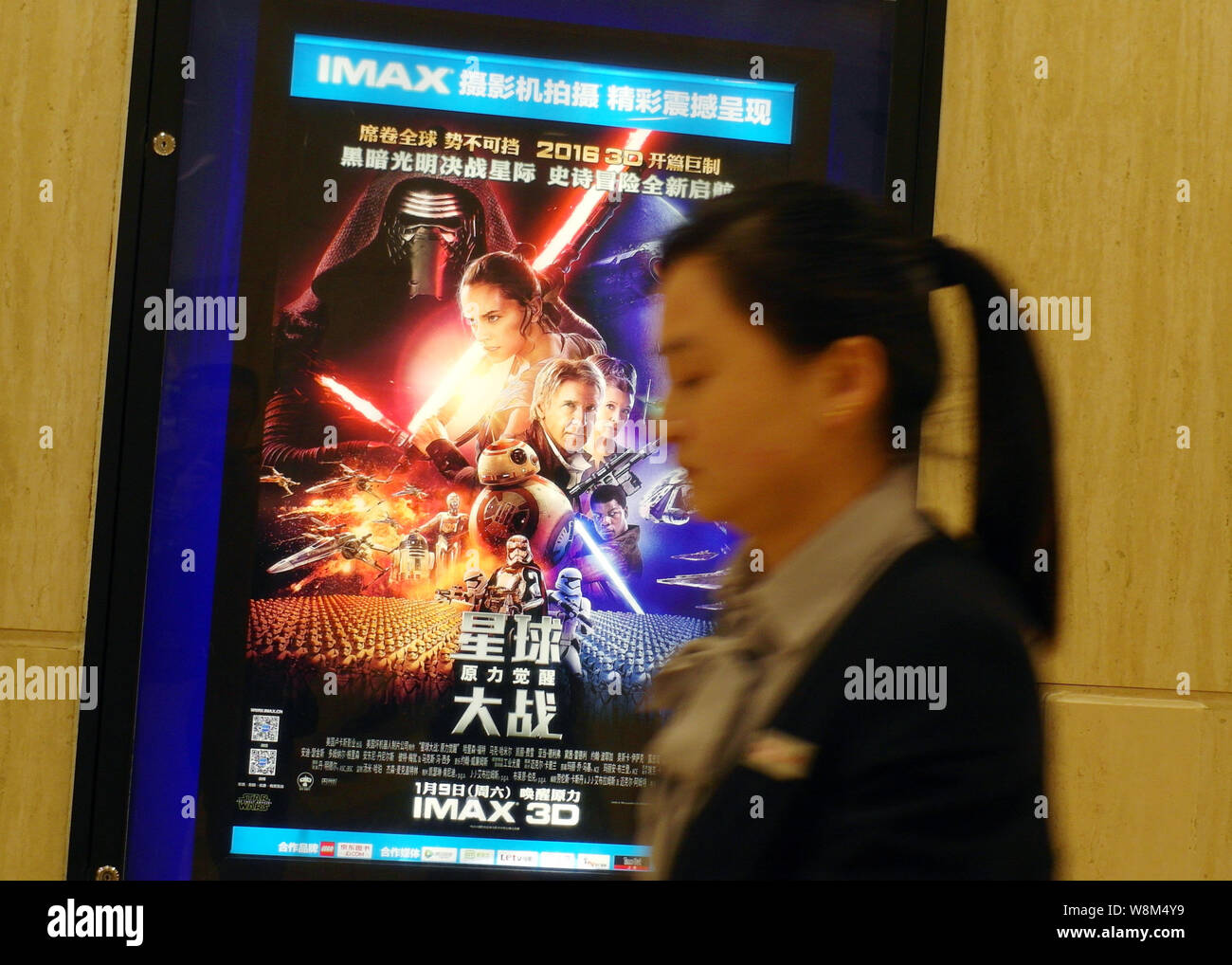 A Chinese Woman Walks Past A Poster Of The Movie Star Wars The Force Awakens At A Cinema In Yichang City Central China S Hubei Province 6 January Stock Photo Alamy