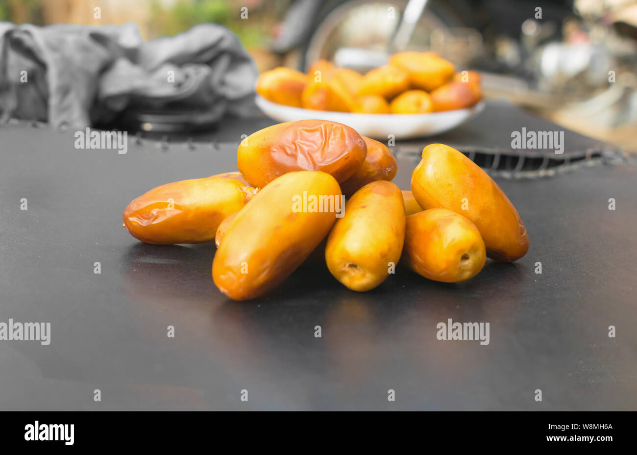 close up of fresh riped delicious  yellow dates  on black background. Stock Photo