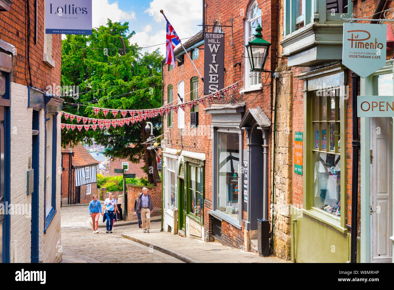 2 July 2019: Lincoln, UK - Steep Hill, the city's famous historic street, with independent shops, cafes and tourists walking up the hill. Stock Photo