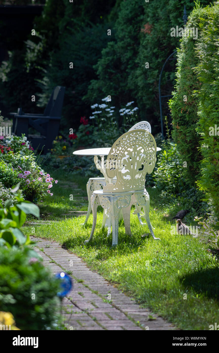 Painted cast iron garden chairs on the backyard Stock Photo ...