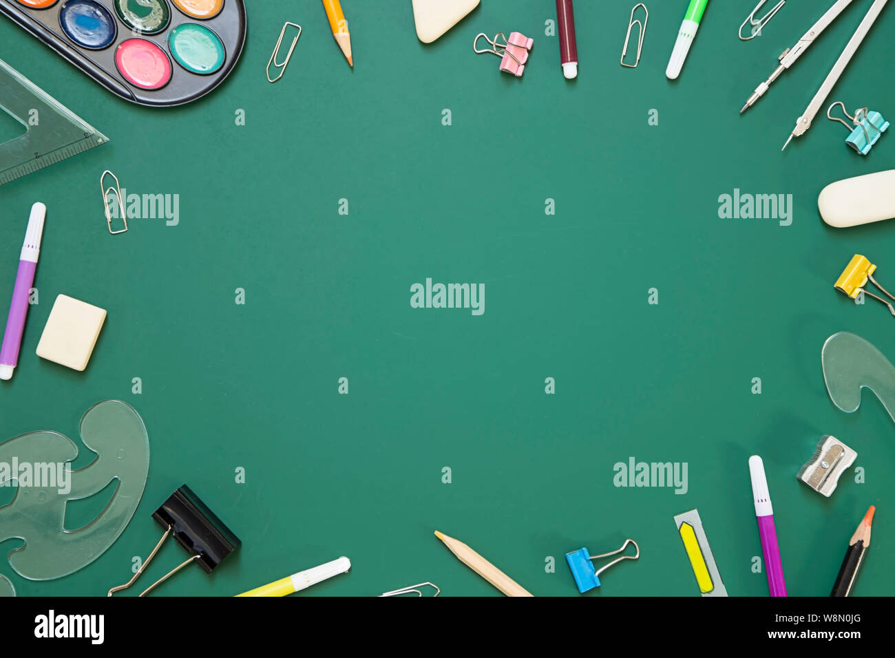 School supplies on green chalkboard  background - top view Stock Photo