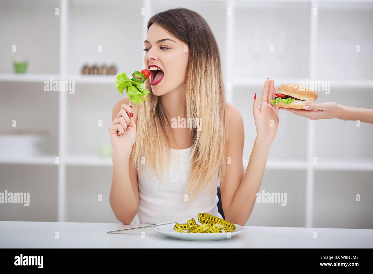 Diet. Healthy eating, dieting, slimming and weigh loss concept. Dieting concept. Weight Loss. The measuring tape is wrapped around the arm. In the Stock Photo