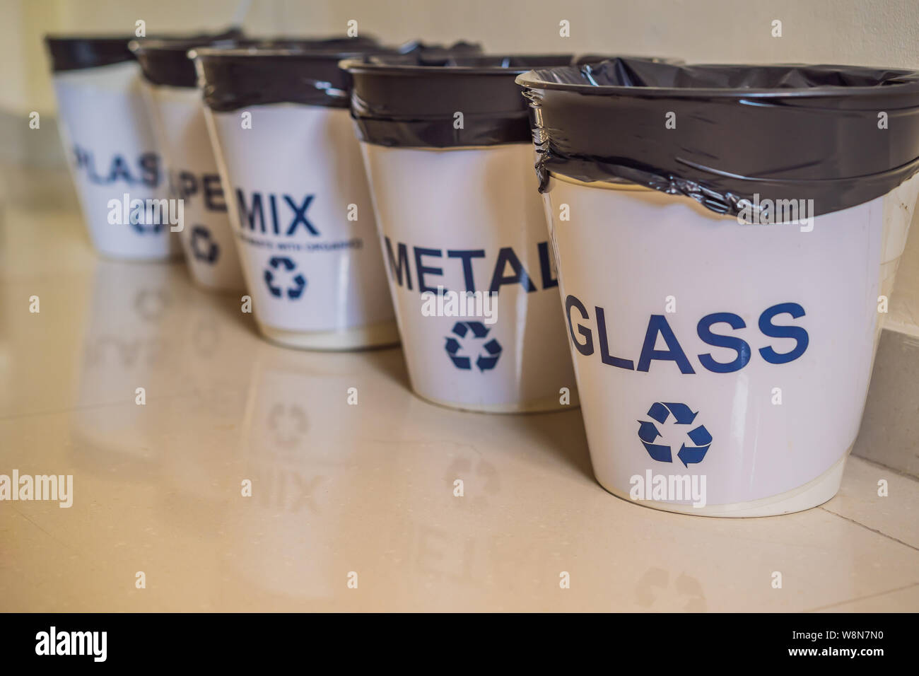Garbage cans. Trash bins with sorted garbage in kitchen cabinet with segregated household garbage - plastic, paper, metal, glass. Ecology and recycle Stock Photo