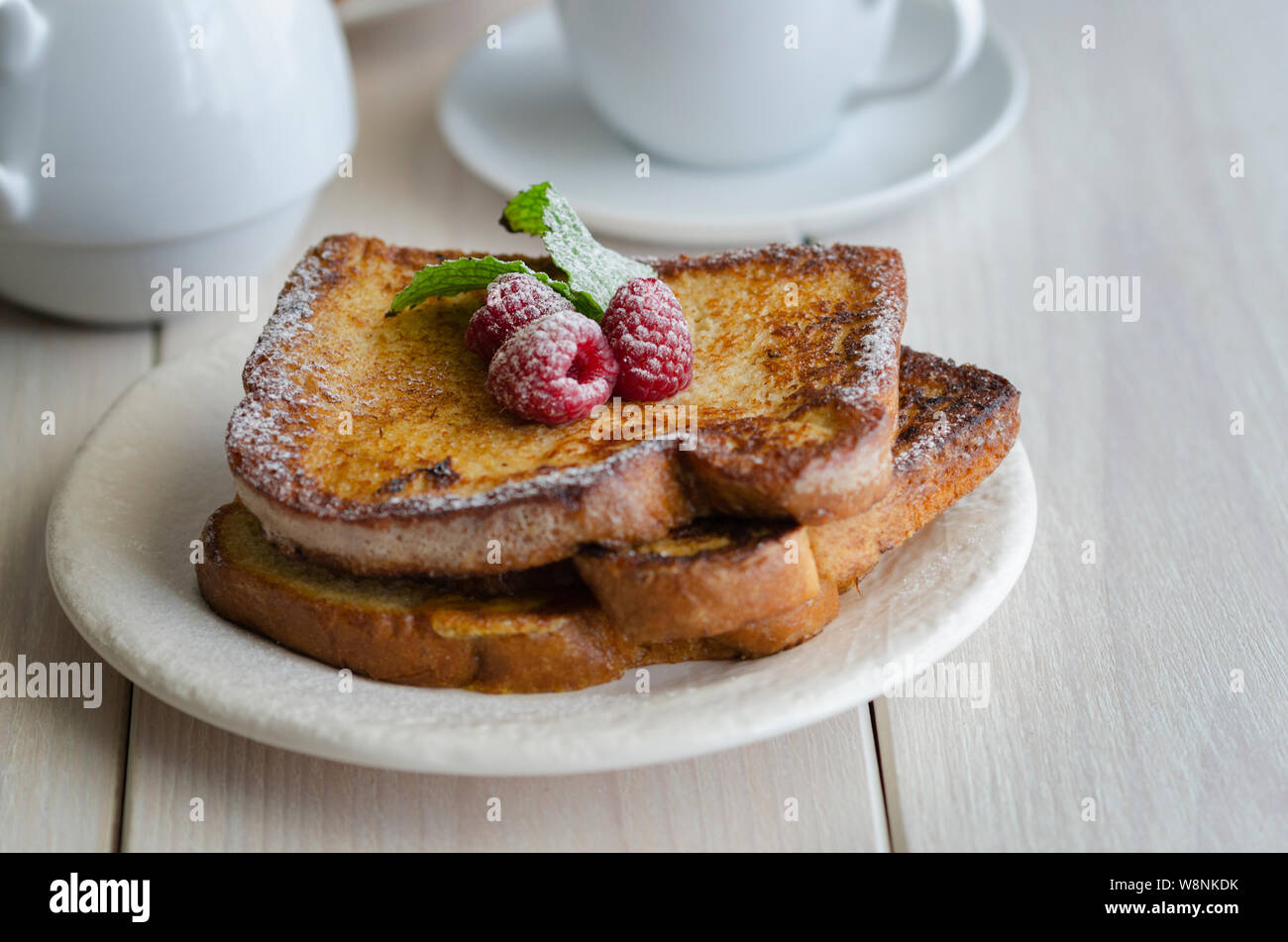 French toast, making with bread soaked in eggs and milk, then fried. Popular sweet dish served decorated with icing sugar and berries served with cup Stock Photo