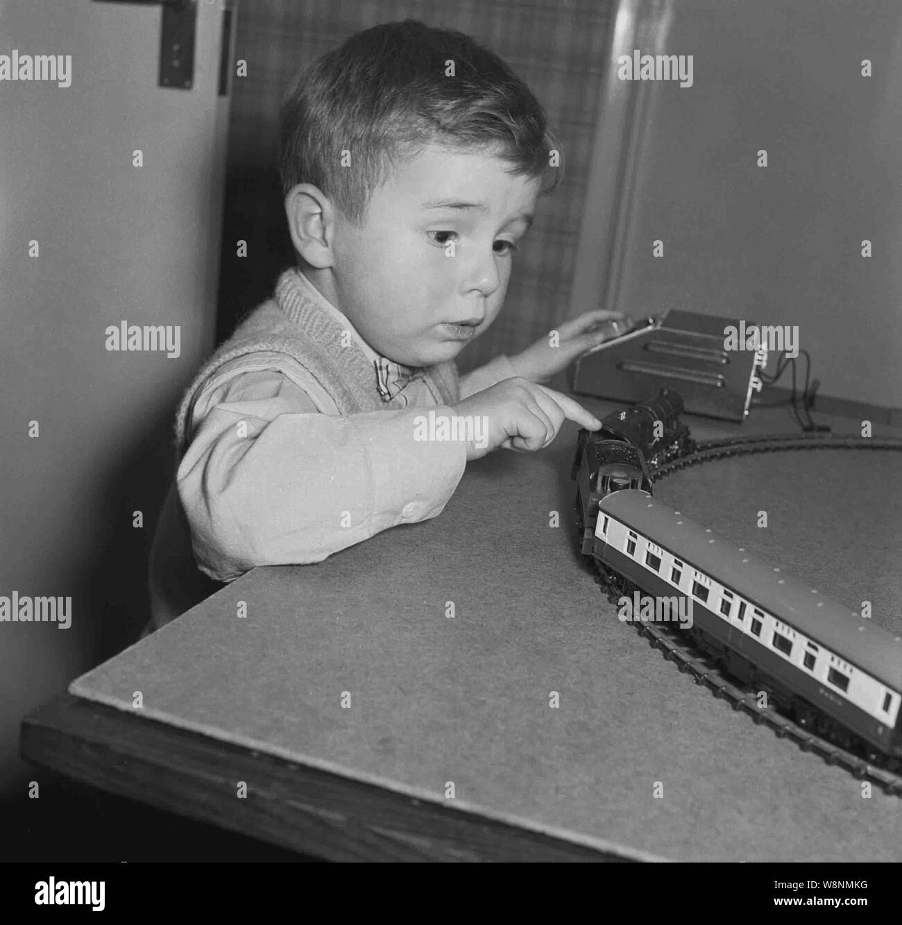 1950s, historical, smartly dressed little boy wearing a bow tie playing with his electric model train set, Engalnd, UK. Stock Photo