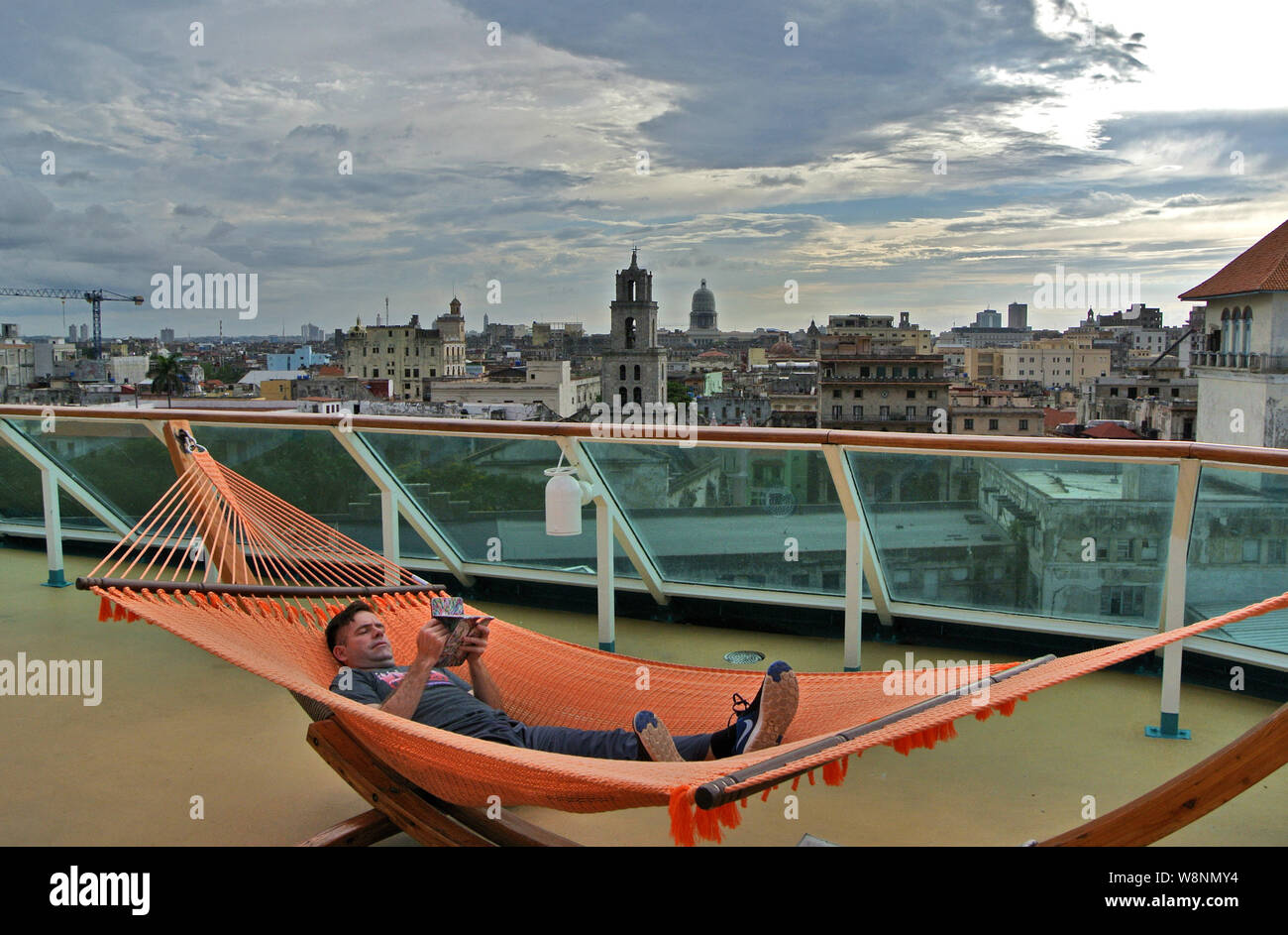 tourist on cruise ship relaxes with glass of wine in hammock on deck overlooking old town havana Stock Photo