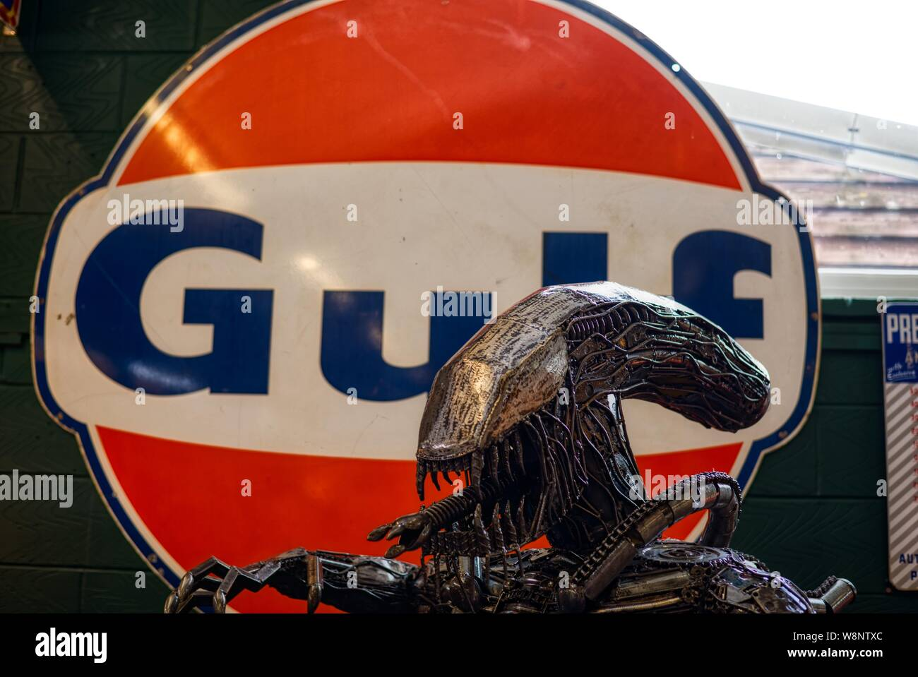 Gulf oil sign and alien in a private car museum at a car show staged by Robert and Tanya Lewis at Old Kiln Farm, Churt, Surrey, UK Stock Photo
