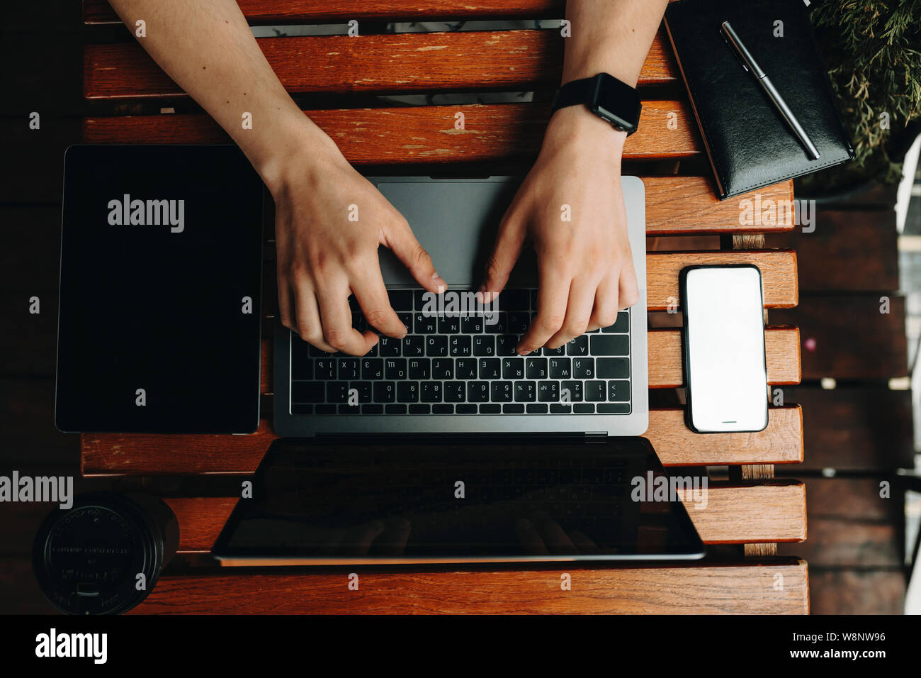 Crop view of male hands using laptop standing on wooden plank table with gadgets and notebook lying around from above Stock Photo