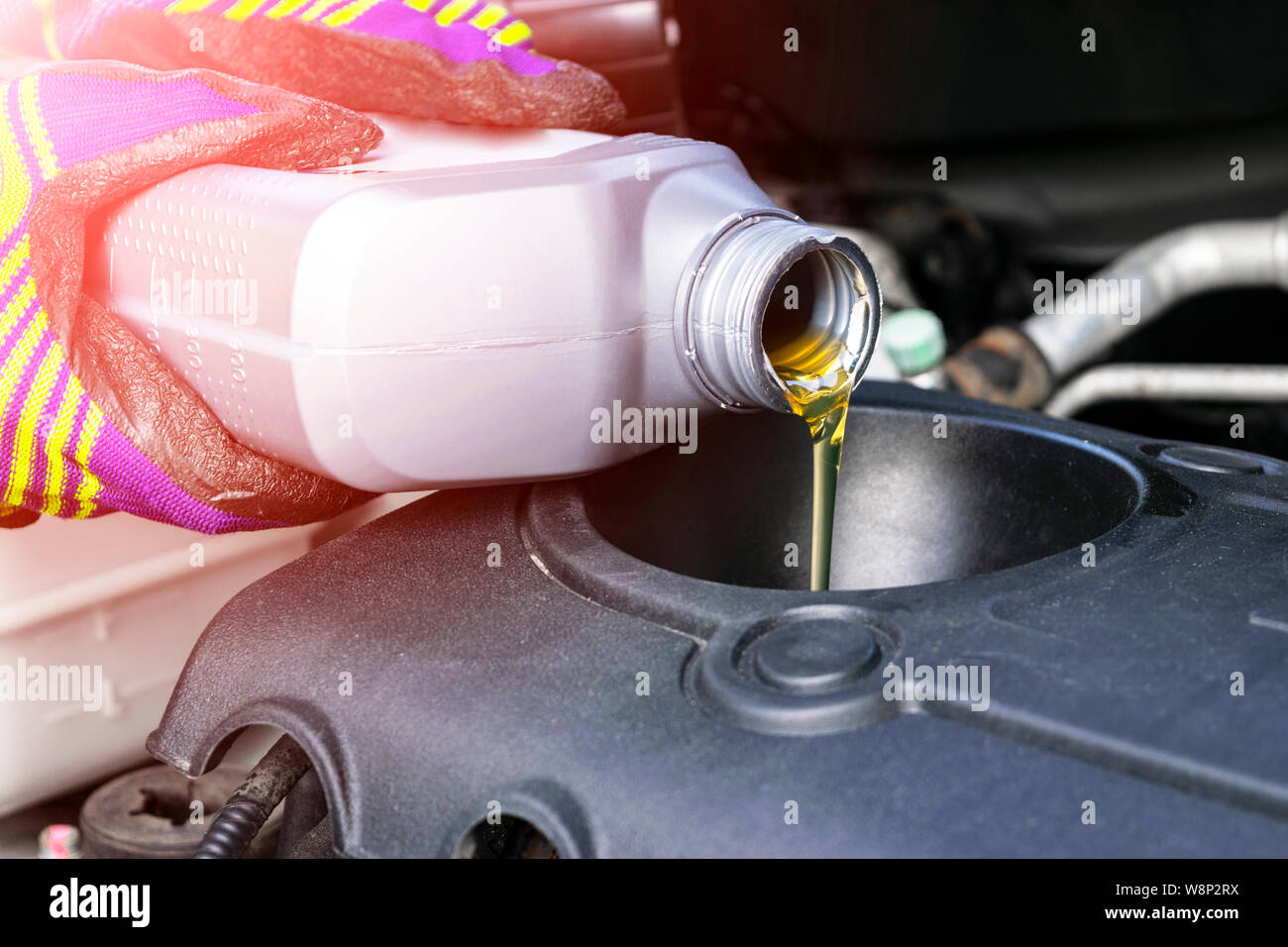 Change the Oil. Hand mechanic in repairing car. Close up oil for car engine. Motor oil pouring to car engine. Refueling and pouring oil into the engin Stock Photo