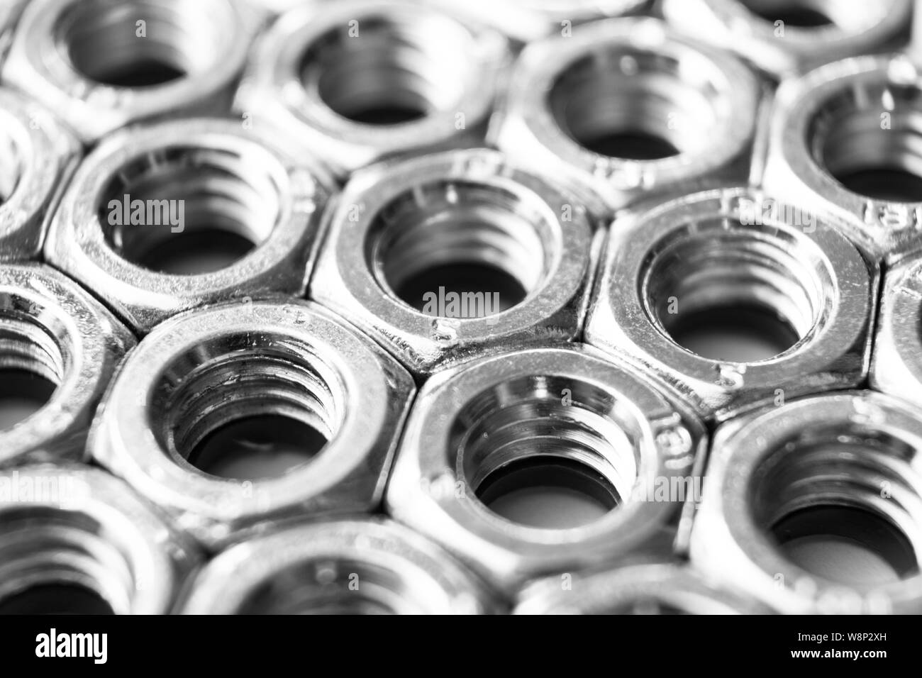 Metal nuts in a row background. Chromed screw nuts isolated. Steel nuts pattern. Set of Nuts and bolts. Tools for work. Black and white Stock Photo