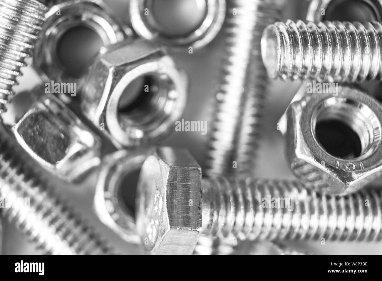 Metal bolts and nuts  in a row background. Chromed screw bolts and nuts isolated. Steel bolts and nuts pattern. Set of Nuts and bolts. Tools for work. Stock Photo