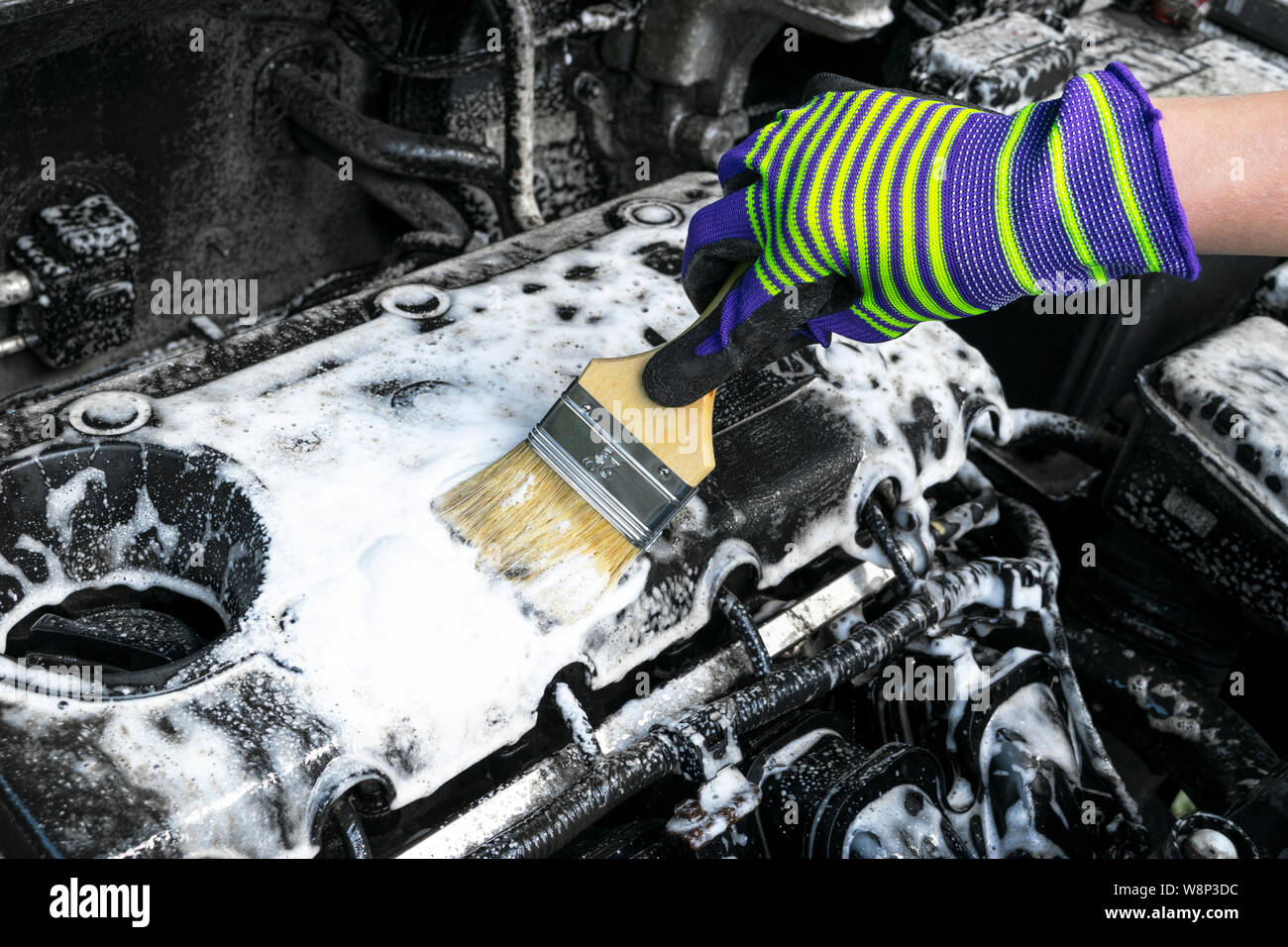 A man cleaning car engine with shampoo and brush. Car detailing or valeting concept. Selective focus. Car detailing. Cleaning with sponge. Worker clea Stock Photo