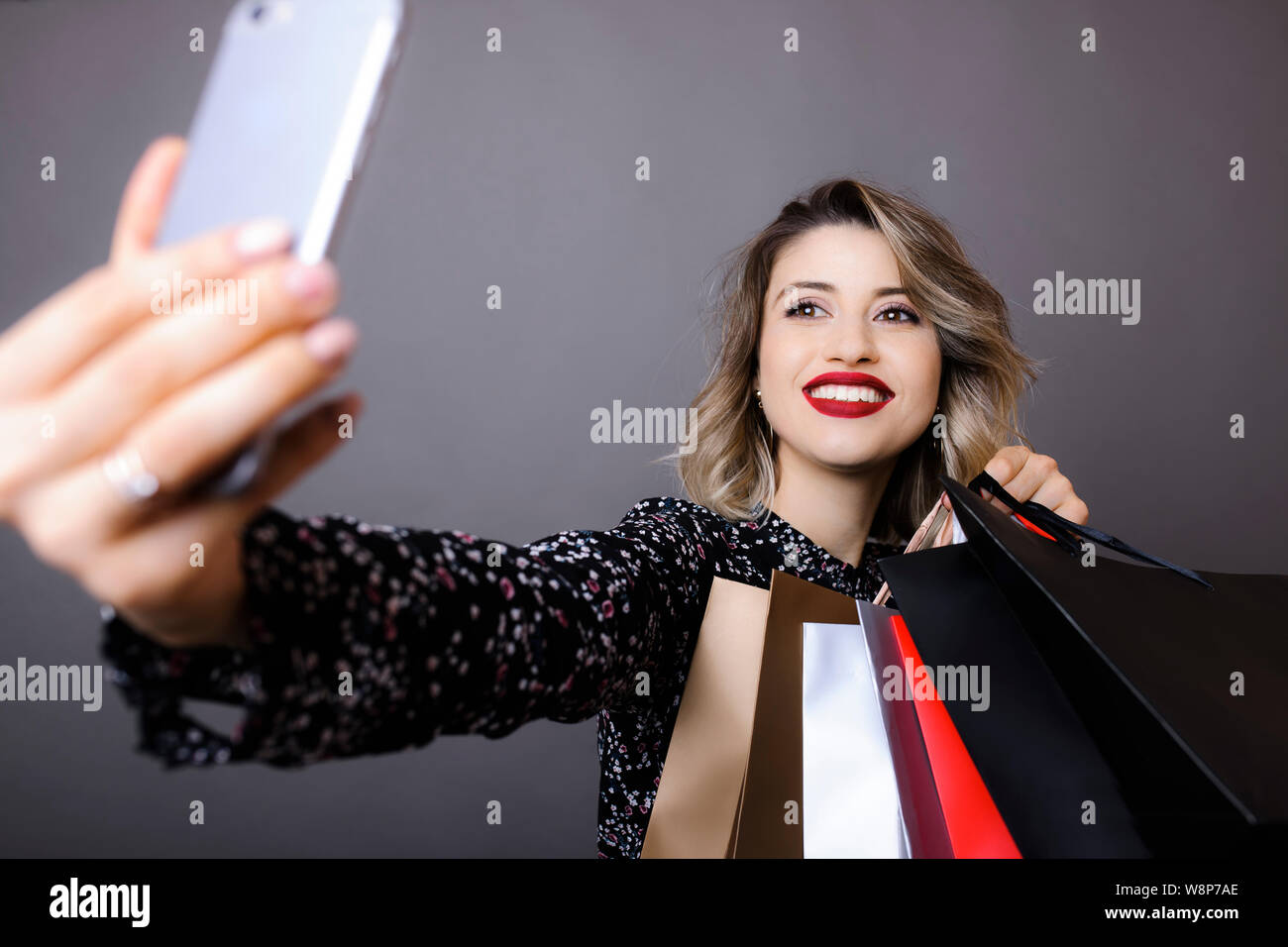 Young smiling woman with bright makeup and curly hair in patterned blouse holding shopping bags and making selfie with mobile phone on gray background Stock Photo