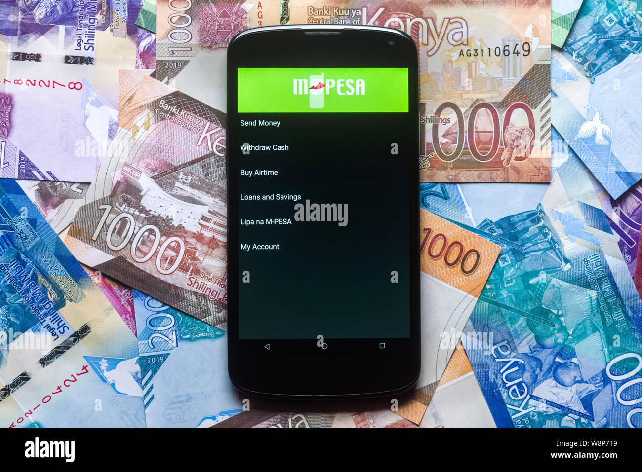 Safaricom M-Pesa fintech microfinance money transaction service on phone with new Kenyan Shilling bank notes background Stock Photo