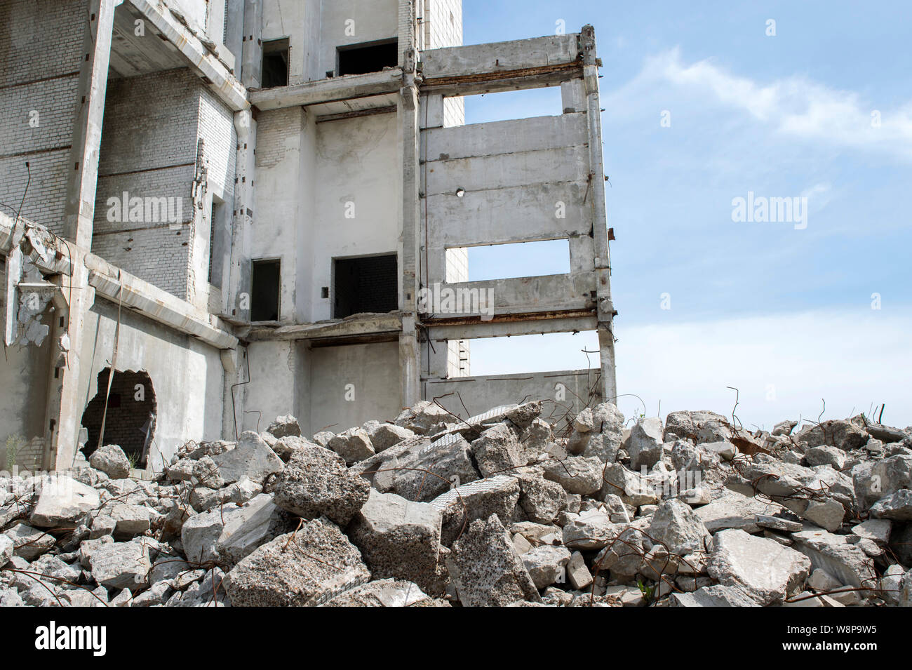 Concrete gray debris close-up on the background of the remains of the destroyed building against the sky. Background Stock Photo