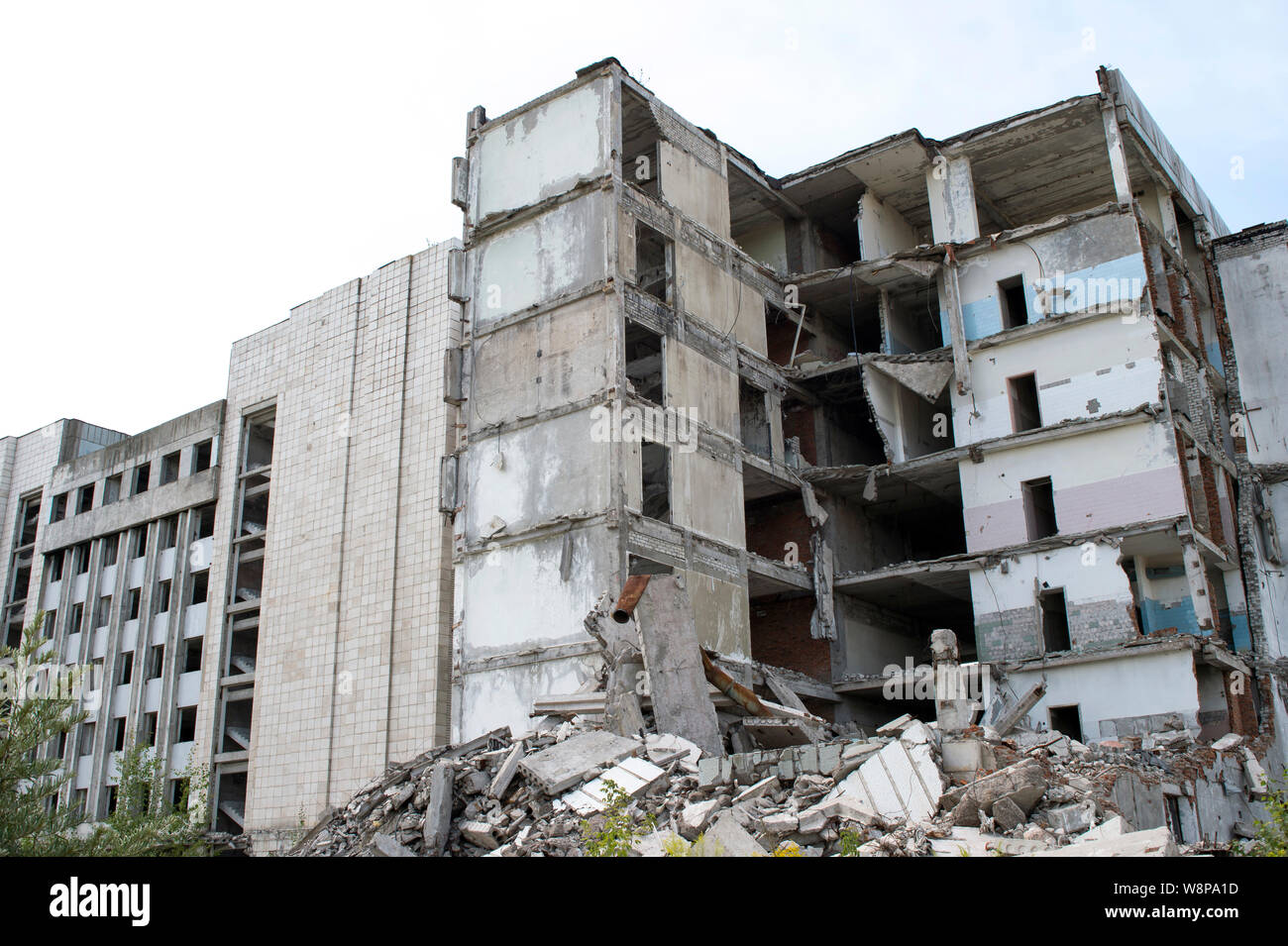 A pile of gray concrete debris with the remains of a large destroyed building. Background Stock Photo