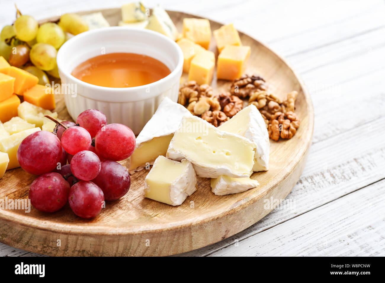 Cheese plate - various types of cheeses with honey, nuts and grapes on a white wooden background closeup Stock Photo
