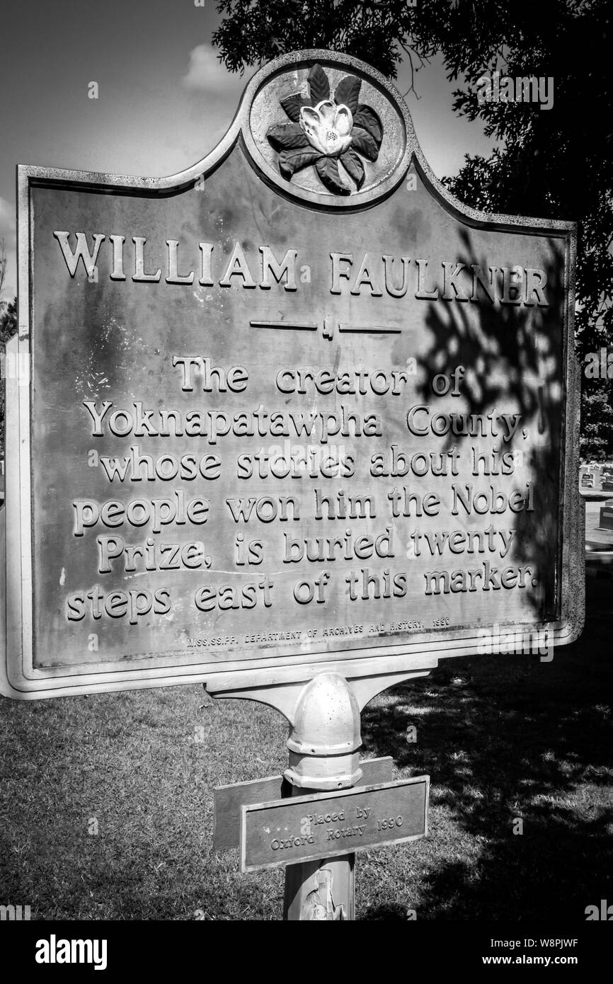 A historic marker noting the nearby burial site of Nobel Prize Laureate, William Faulkner, in his hometown of Oxford, MS, black and white Stock Photo