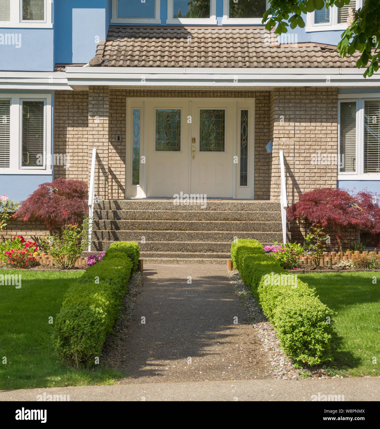 Entrance of family house with small hedges on sides in suburban area Stock Photo