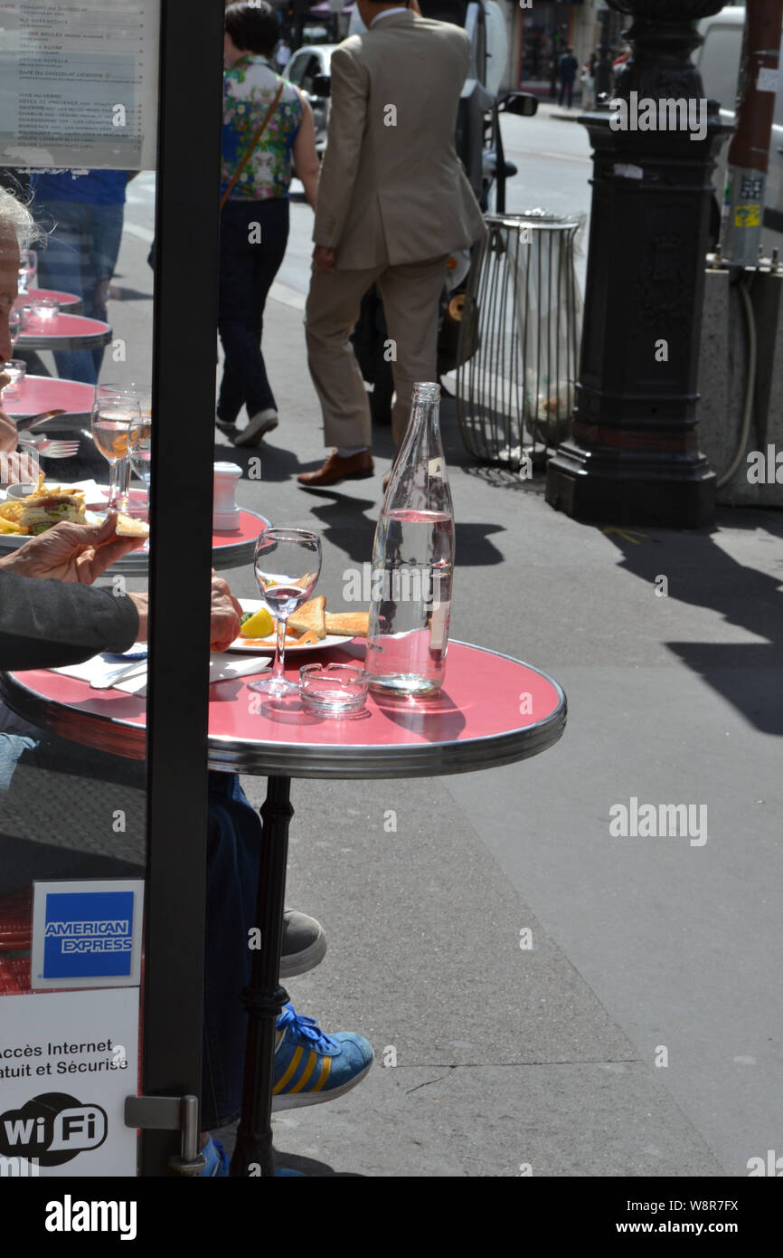 Paris/France - August 19, 2014: Close-up view to tables of a street cafe in Paris in a sunny summer day with tourists eating snack. Stock Photo