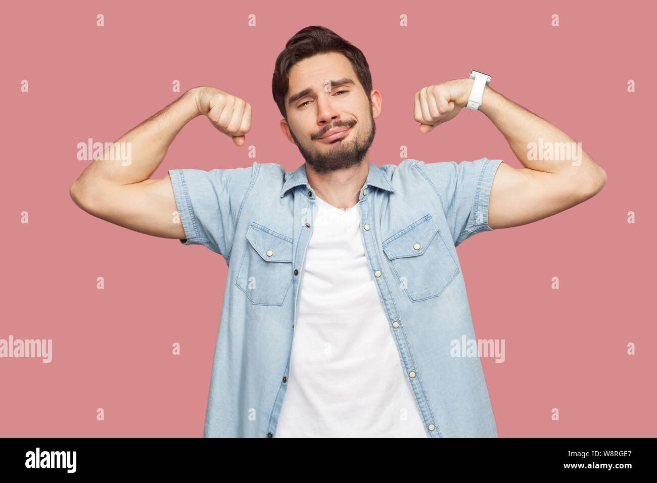 Portrait Of Proud Satisfied Handsome Bearded Young Man In Blue Casual Style Shirt Standing In Body Building Pose And Showing His Strongness Indoor St Stock Photo Alamy