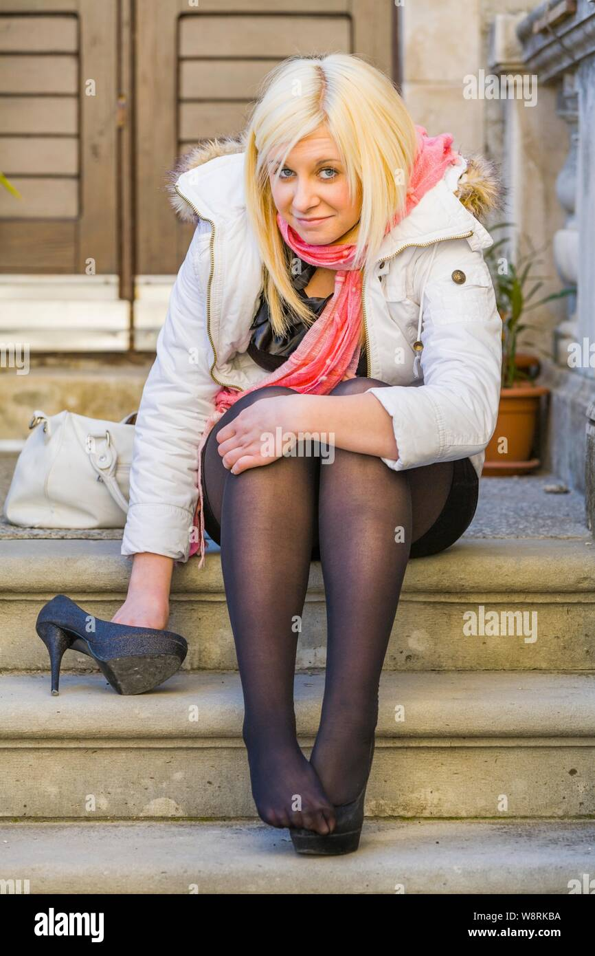 Young blonde woman one single solo person detached high-heeled heels shoe sitting smiling smile looking at camera eye eyes contact Stock Photo