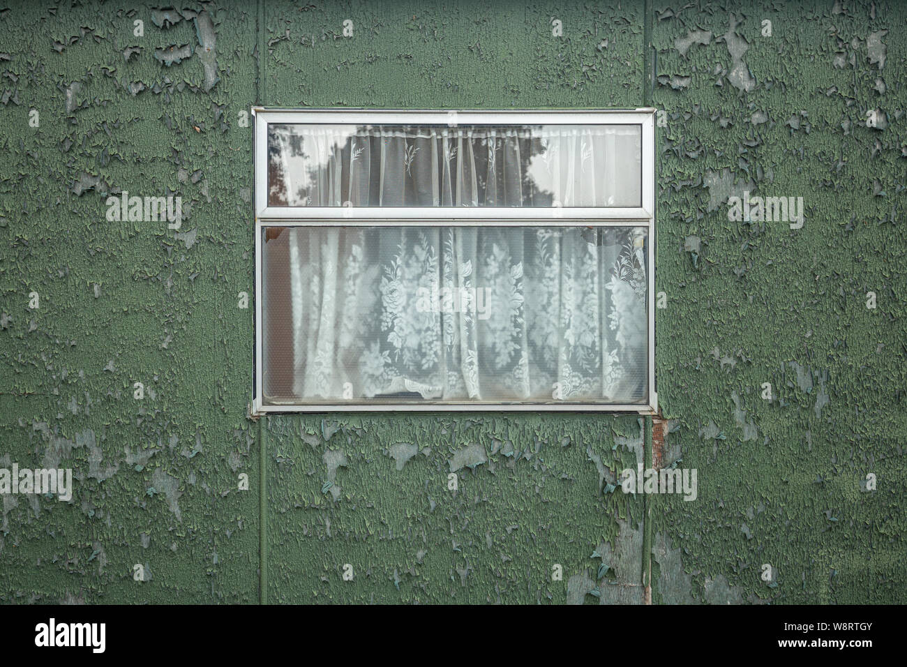 Old glassed window with net curtain on flaky wall background Stock Photo