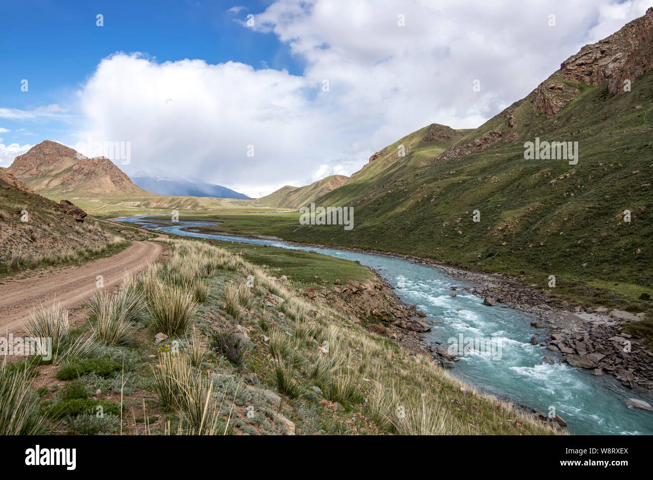 View of the river flowing between green hills with grass and stones in the foreground Kyrgyzstan. Tien Shan Stock Photo