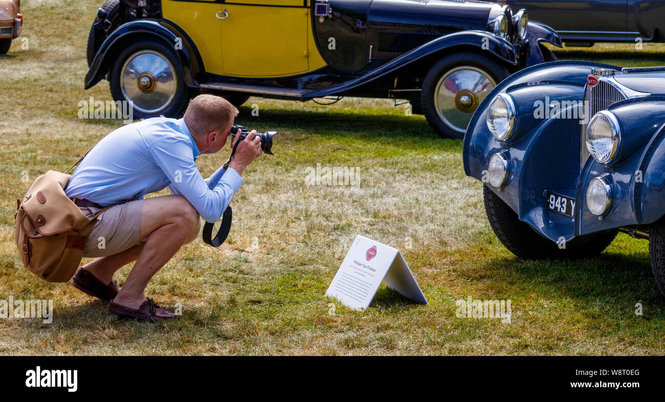Photographer taking an image of the 1936 Bugatti Type 57S Atlantic in the Cartier Style et Luxe competition. 2019 Foodwood Festival of Speed, Sussex. Stock Photo