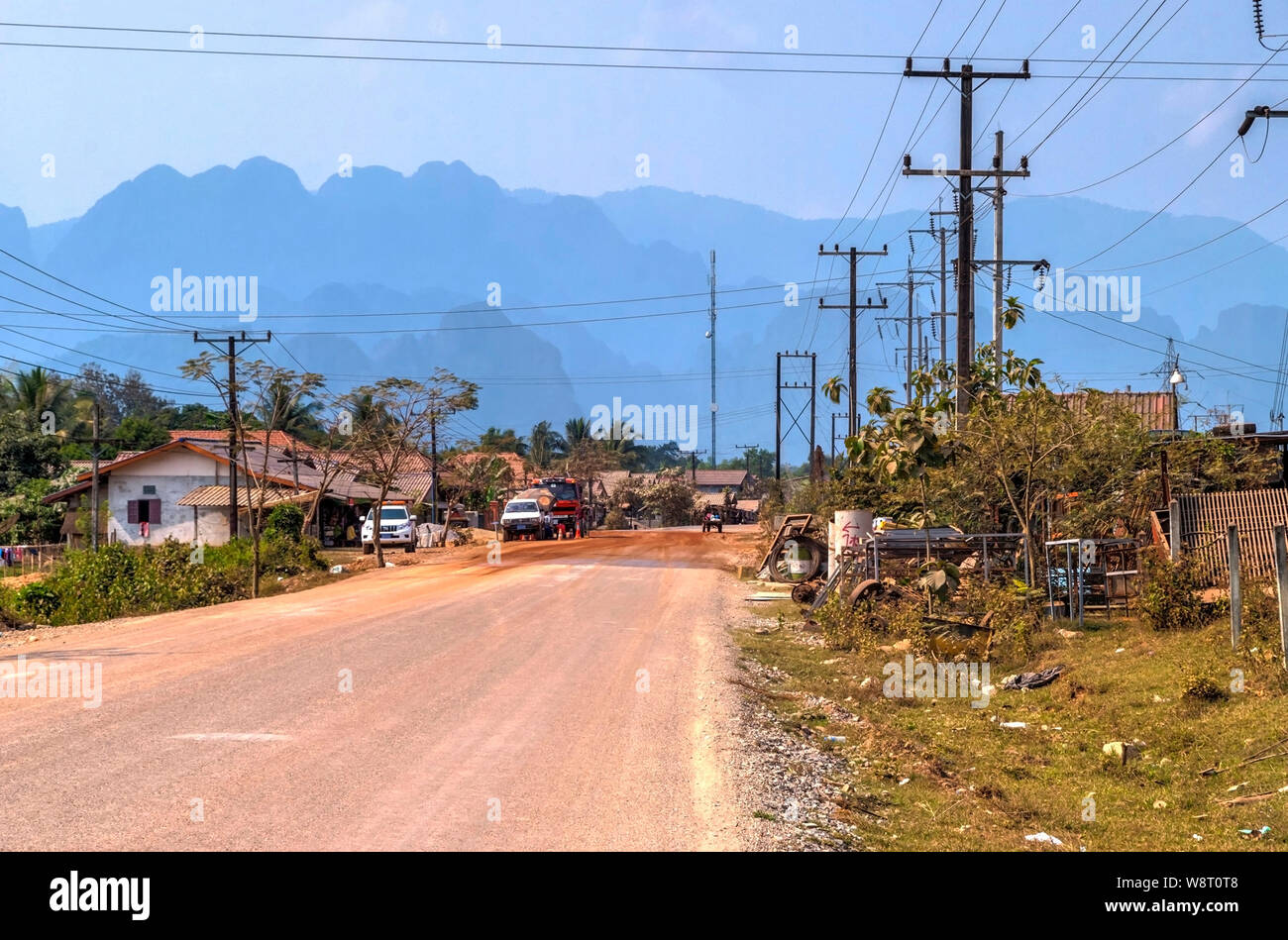 Driving thru laotian village and scenic hills in the horizon Stock Photo