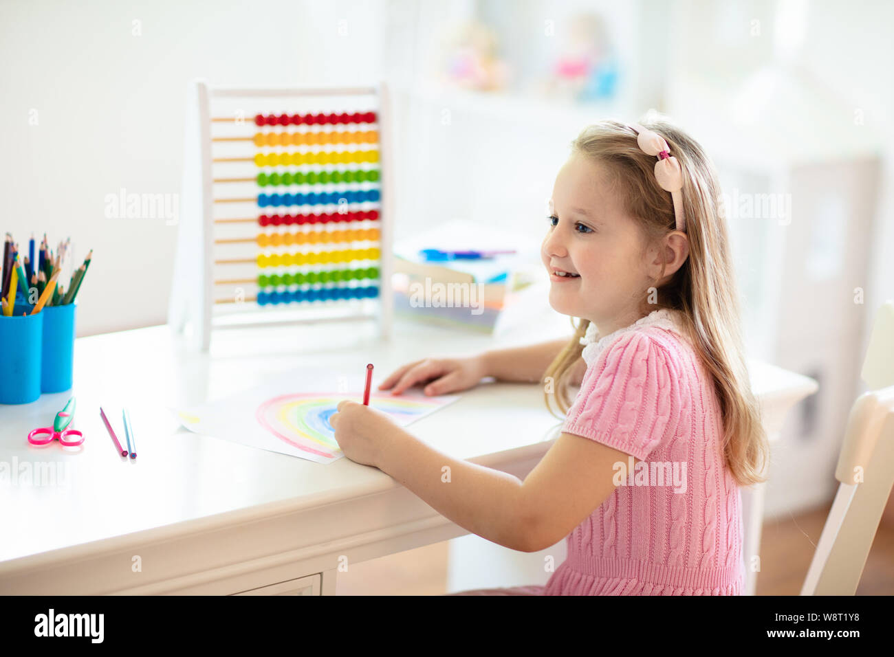 Child drawing rainbow. Kid painting at home. Little girl ...